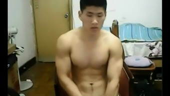 Beefy Oriental hunk departs his clothes and bad boys off his prick