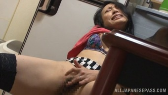 Lustful Asian cougar in dress fondling her large titties before masturbating incredibly with the food prep