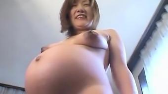 Oriental preggo plays with her titties