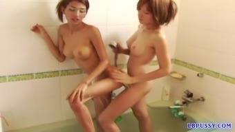 Kissing and touching, these two ladyboy lesbians rub their goods while soaking wet.