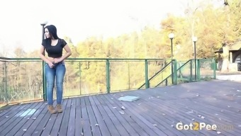 Full-figured and busty blonde girl located on the decking makes a puddle